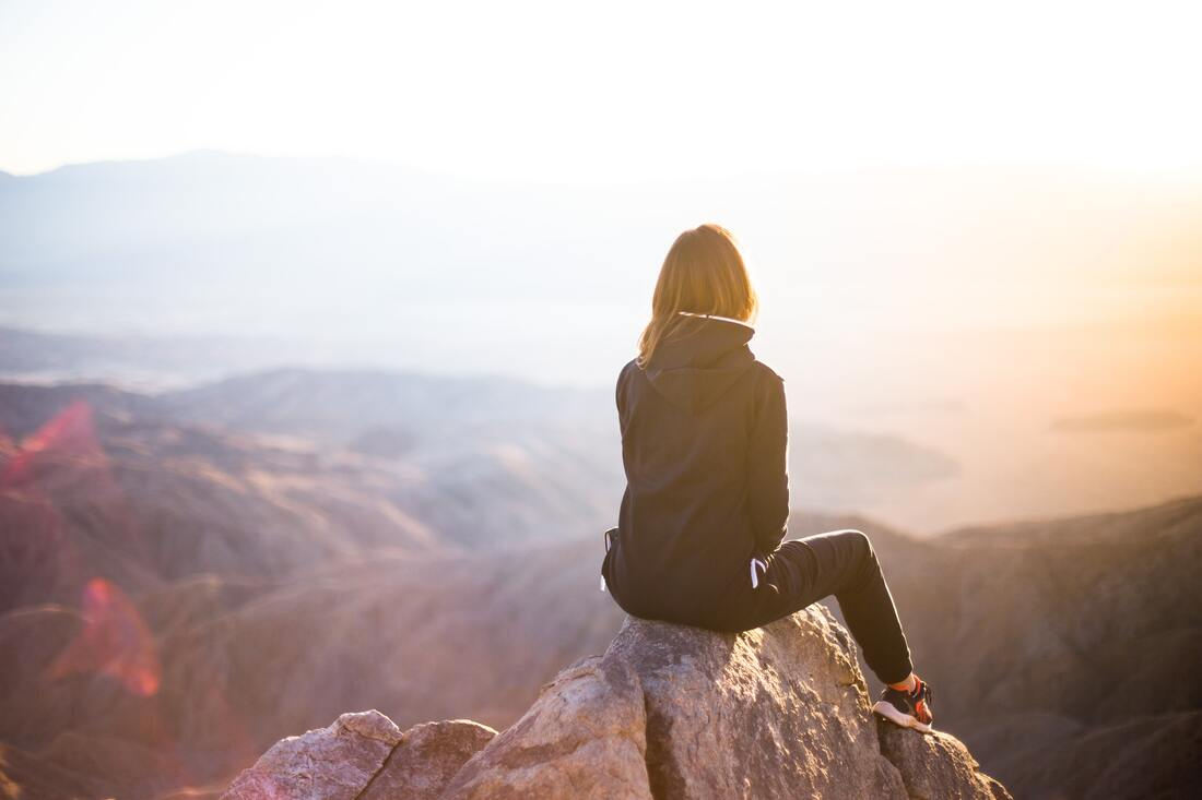 Girl sitting on a rock gazing at a mountain landscape, illustrating blog theme, 'Declutter your Mind'.