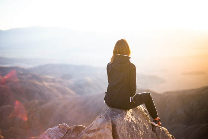 Girl sitting on a rock gazing at the mountains, illustrating the theme, 'Take every thought captive'.
