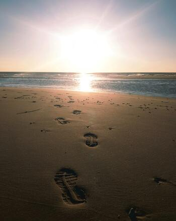 Footprints on the empty sand, illustrating the need for a quiet space to be alone with God.