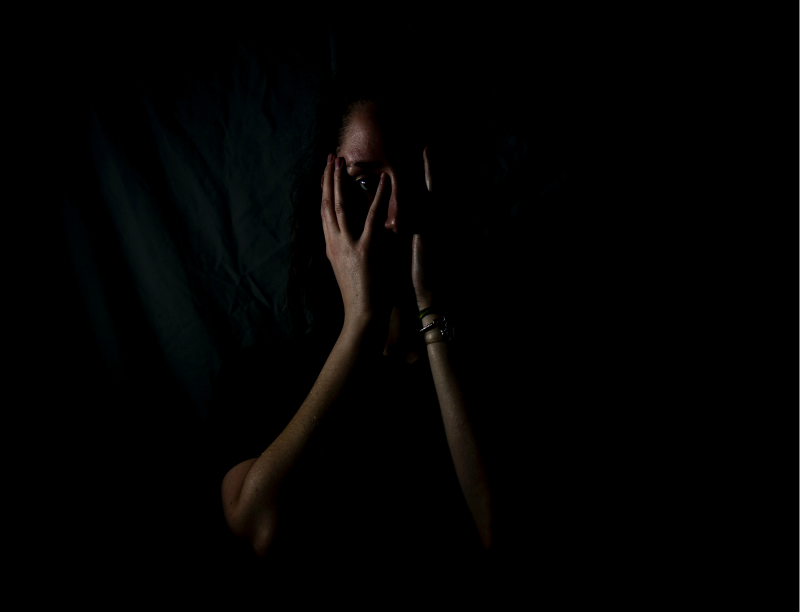 Girl in darkened room, with her face in her hands, illustrating 'Free from Fear' topic.