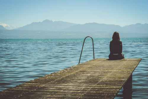 Girl sitting solo on a pier, looking out over the sea to mountains beyond, illustrating 'how to love being alone'.