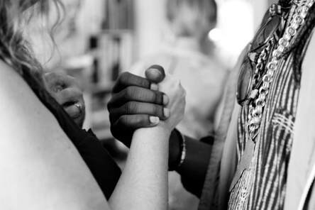 2 women from different ethnic groups, clasping hands, illustrating the community of believers is inclusive.